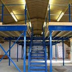 an image of a mezzanine floor with blue steel supports and a wooden level