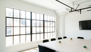 an image of a modern office interior with a large window and conference table