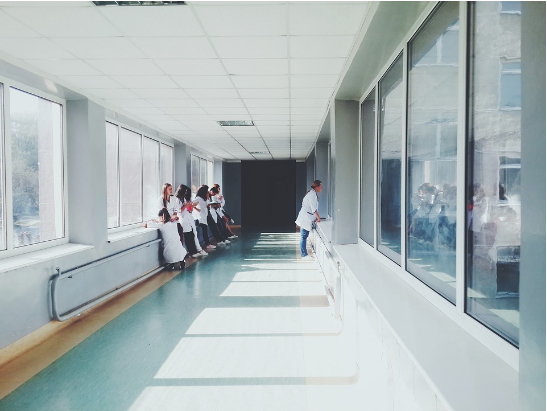 an image of a hallway in a hospital, which is light because of large windows and a light-colours suspended ceiling